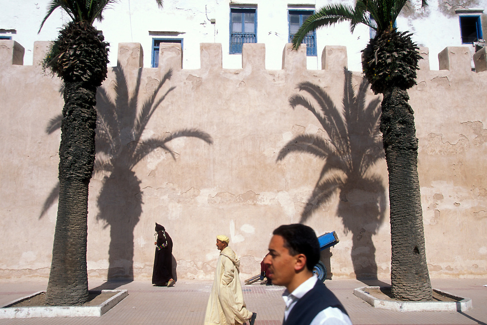 Africa, Morocco, Men wearing djellabas walk past shadows of palm trees on ancient walled medina in Essaouira