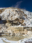 Mammouth Hot Springs travertine terrace, calcium carbonate forms white/tan hillside, thermal