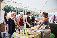 "ROME, ITALY - 3 JULY 2016: Gipsy Queen member Aninfa Hokic (31) serves a customer at a food stand at the iFest, an alternative music festival  in Rome, Italy, on July 3rd 2016.<br /> <br /> The Gipsy Queens are a travelling catering business founded by Roma women in Rome.<br /> <br /> In 2015 Arci Solidarietà, an independent association for the promotion of social development, launched the ""Tavolo delle donne rom"" (Round table of Roma women) to both incentivise the process of integration of Roma in the city of Rome and to strengthen the Roma women's self-esteem in the context of a culture tied to patriarchal models. The ""Gipsy Queens"" project was founded by ten Roma women in July 2015 after an event organised together with Arci Solidarietà in the Candoni Roma camp in the Magliana, a neighbourhood in the South-West periphery of Rome, during which people were invited to dance and eat Roma cuisine. The goal of the Gipsy Queen travelling catering business is to support equal opportunities and female entrepreneurship among Roma women, who are often relegated to the roles of wives and mothers."