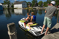 Rick and Jaclyn Deutsch get a push off the dock by Joe Wadlinger of Wolfeboro Jet Ski Rentals as they head out from the Back Bay on their rental Sea-Doo.  (Karen Bobotas/Photographer)