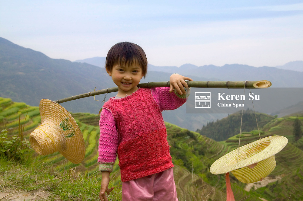 Little girl carrying shoulder pole with straw hats, rice terraces at back, Longsheng, Guangxi Province, China