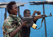 A Liberian government gunman at the 'Old Bridge' screams insults at the enemy whilst firing at LURD forces as a fellow gunman celebrates the gunfire in the background Monrovia 30 July 2003.This the Twelveth day of continued fighting for the capital despite the call for ceasefire. Battles are centred around the New, Old and Stockton bridges leading into the city.<br /> EPA PHOTO/NIC BOTHMA