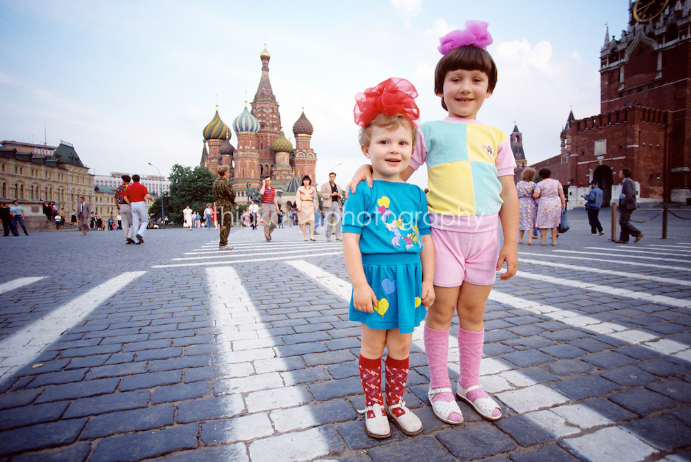 Little girls dressed with bows and bright outfits pose infront of St. Basil's Cathedral, Red Square, Moscow, Russia