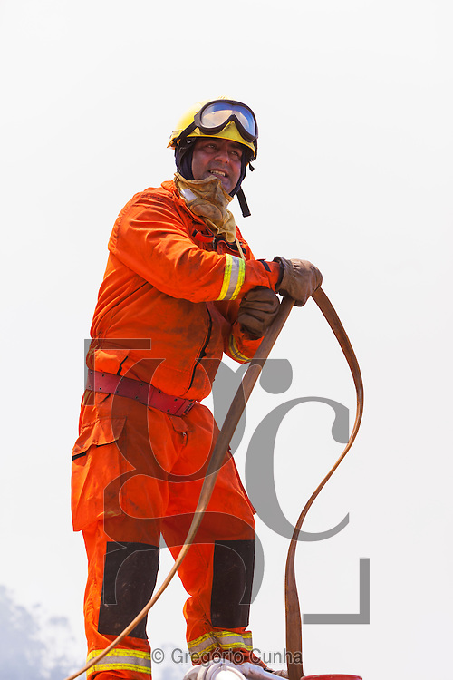PORTUGAL, Porto Moniz : A fireman stands on a fire truck as he works to extinguish a forest fire in Achadas da Cruz, close to Porto Moniz, on Madeira Island on July 20, 2012. Fires raged around the towns of Calheta, Ribeira Brava and in Santa Cruz, where one house was destroyed and a health centre, school and youth centre were evacuated as a precautionary measure. The problems began on the evening of July 18 when high temperatures and strong winds fanned a fire that broke out on the edge of the capital Funchal, gutting two houses and partially burning a third. PHOTO / GREGORIO CUNHA