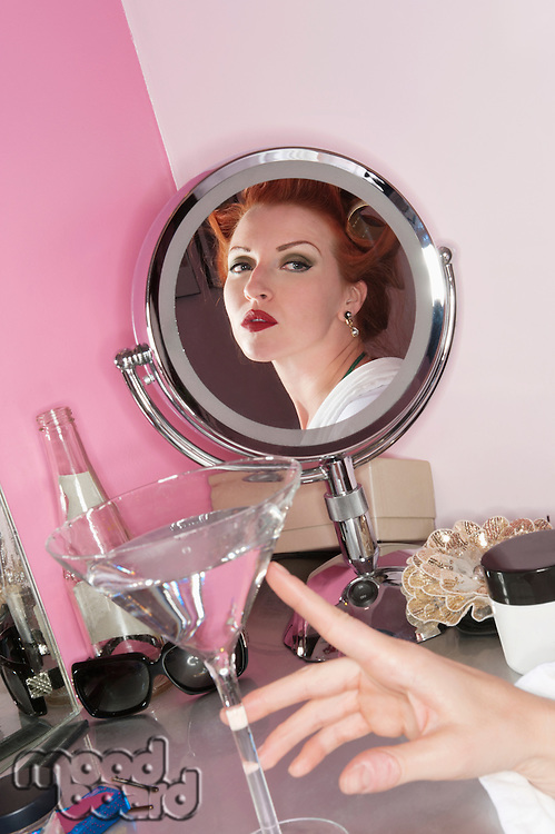 Reflection of beautiful woman in the mirror with martini glass on table