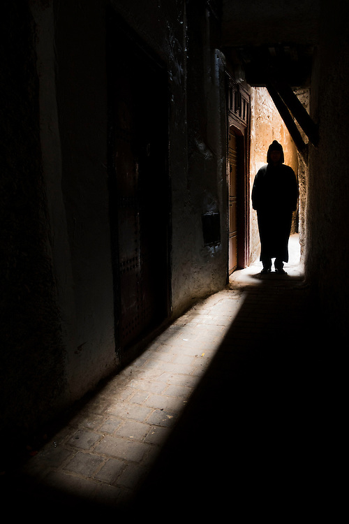 A lone figure waits in a dark alley, Fes, Morocco.