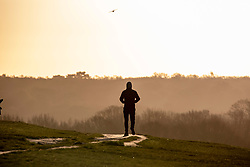 © Licensed to London News Pictures. 12/02/2020. London, UK. A walker in the calm early morning light in Richmond Park as the Met Office issue another weather warning for Storm Dennis with high winds and heavy rain to hit the South East again this weekend. Photo credit: Alex Lentati/LNP