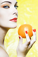 beautiful caucasian woman portrait showing a  orange tangerine fruit studio on yellow background
