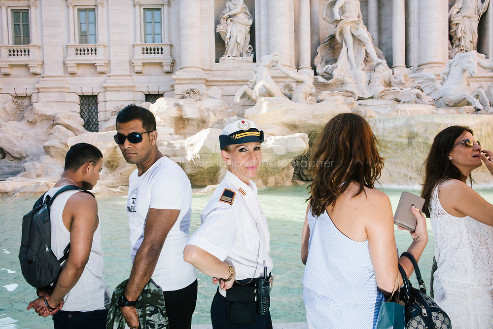 ROME, ITALY - 20 JUNE 2017: A Roman policewoman, entrusted to protect the Fountain of Trevi, is seen here by the fountain in Rome, Italy, on June 20th 2017.<br /> <br /> The warm weather has brought a menacing whiff of tourists behaving badly in Rome. On April 12, a man went skinny-dipping in the Trevi fountain resulting in a viral web video and a 500 euro fine.<br /> <br /> Virginia Raggi, the mayor of Rome and a national figurehead of the anti-establishment Five Star Movement,  issued an ordinance involving harsher fines for eating, drinking or sitting on the fountains, for washing animals or clothes in the fountain water or for throwing anything other than coins into the water of the Trevi Fountain, Bernini&rsquo;s Four Fountains and 35 other city fountains of artistic or historic significance around the city.  &ldquo;It is unacceptable that someone use them to go swimming or clean themselves, it&rsquo;s an historic patrimony that we must safeguard,&rdquo; Ms. Raggi said.