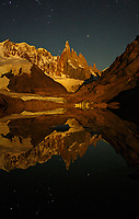 On an unusually windstill night, in an area that often is buffeted by gale force winds, Cerro Torre is bathed in the light of the rising moon, while the stars reflect beautifully in Laguna Torre's calm waters.