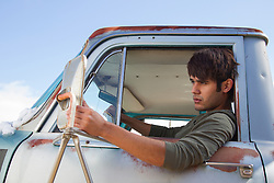 young man in sitting in a truck looking at himself in the rear view mirror