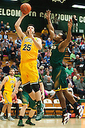 Vermont's Drew Urquhart (25) leaps over Lyndon's Alexis Ravelo (5) for a lay up during the men's basketball game between the Lyndon State Hornets and the Vermont Catamounts at Patrick Gym on Saturday afternoon November 19, 2016 in Burlington (BRIAN JENKINS/for the FREE PRESS)