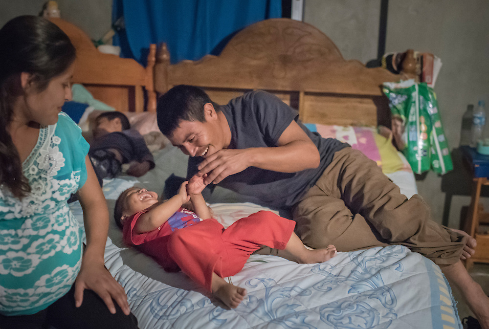 As Leandro sleeps, Santiago Garcia tickles Josue before bedtime in the family's shared bedroom in Santa Ana. Santiago Garcia built his family's home on the same plot of land that his parents own, and he intends to call this home for the rest of his life. Nick Wagner / Alexia Foundation