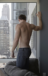 shirtless man at home in an apartment in New York City
