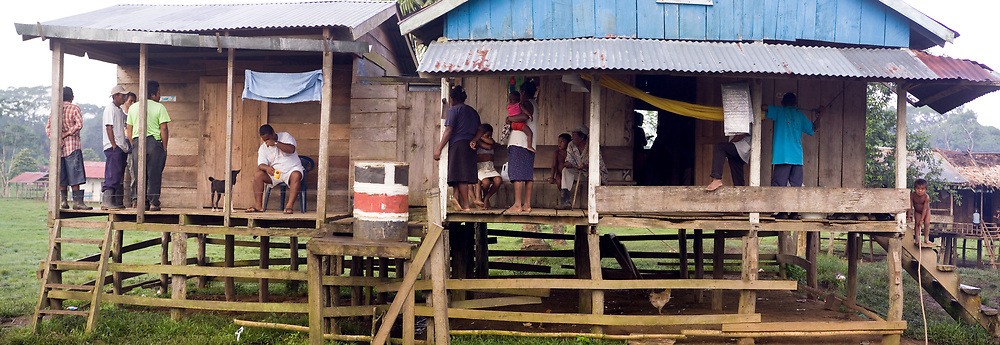 Several people gather outside of homes on stilts in the remote indigenous Miskito village in Krin Krin, Nicaragua, located on the Rio Coco. Lumber for homes are cut and sized by hand, using machetes, axes and saws. A typical one-room house will be home to anywhere from three to six families. The area continues to struggle with famine, preventable diseases, lack of clean drinking water, and no access to healthcare, worsened by crop failure in recent years.