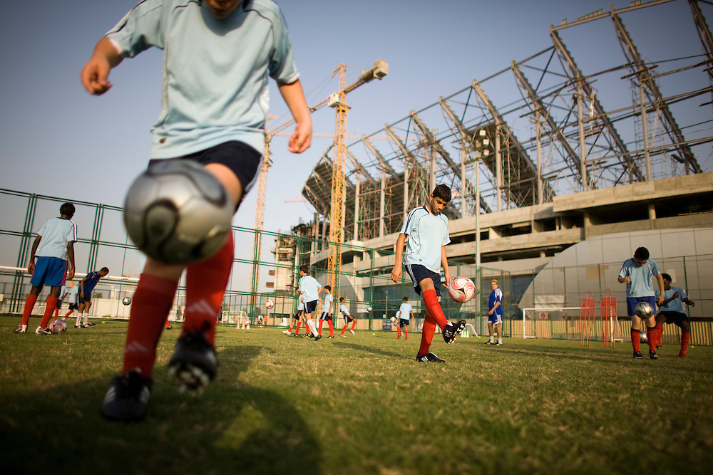 Football  taught to school  cildern  in the  shadow of the  new Sports stadium  one of many public projects being built.