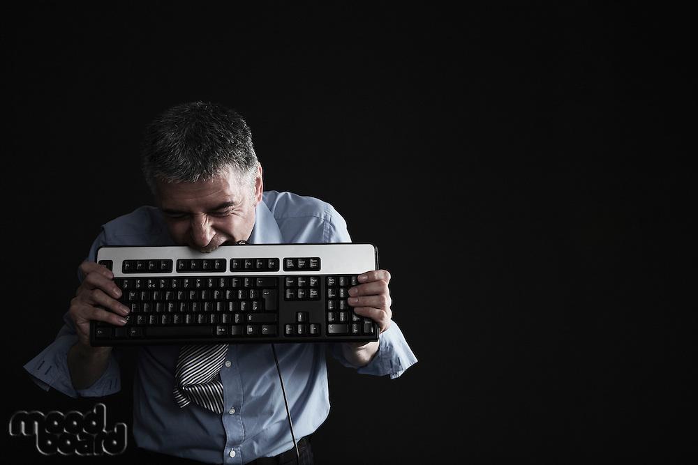 Worried Businessman Biting a Computer Keyboard