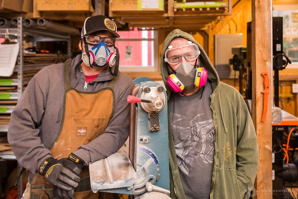 EJ (l) and Travis in full protective gear, including a heavy duty apron, breathing masks, eye protection and earplugs in preparation to use the belt sander, which produces significant noise, dust and even sparks.