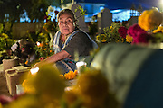 An elderly woman reflects at the gravesite of a relative at Xoxocatian cemetery decorated with flowers and candles for the Day of the Dead Festival known in spanish as Día de Muertos on October 31, 2014 in Oaxaca, Mexico.