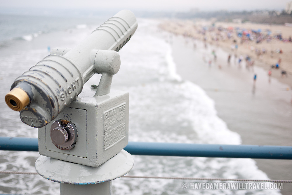 A coin operated telescope on Santa Monica pier overlooking the crowds of people on the beach and surf of Santa Monica. The focus is on the telescope, with the people and beach beyond being blurred.