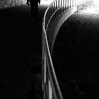 A lone man walking through a pedestrian underpass beside a curved railed fence, into the light