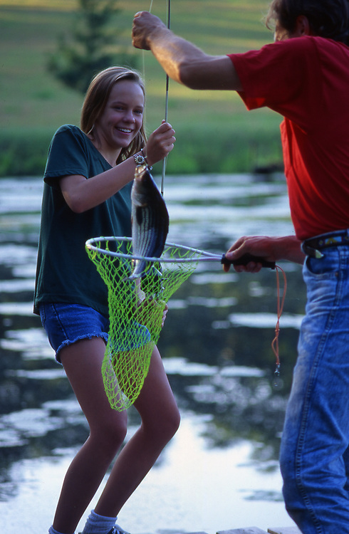 Father and daughter catch fish at farm lake, York Co., Pennsylvania