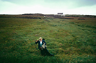 Peat digger walking across field, Ireland