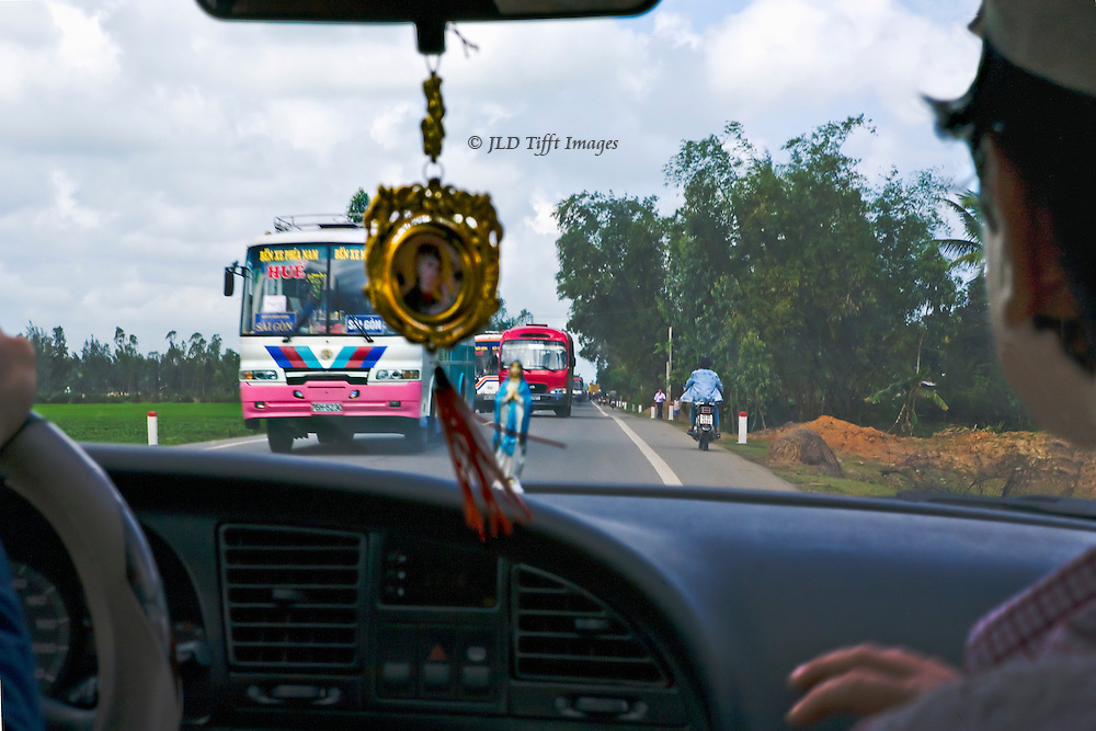 Traffic on Route 1, the main north-south highway in Vietnam.  Aggressive and speeding buses take precedence over cars, pedestrians, and cyclists, seen from inside a passenger car going the other way.