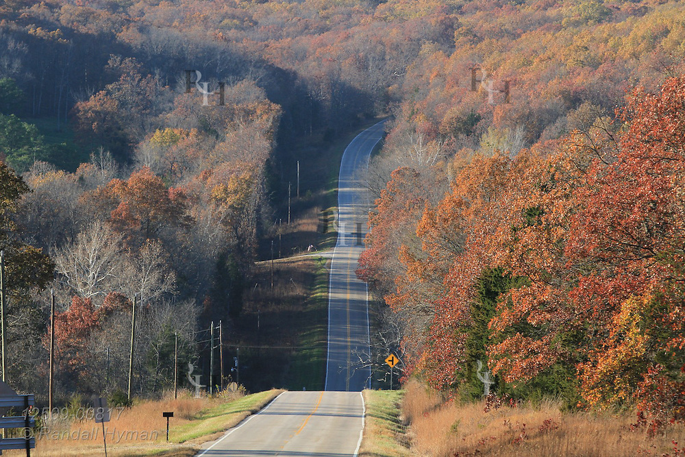 Rural highway cuts through hilly Ozark woodlands in autumn Viburnum, Missouri.