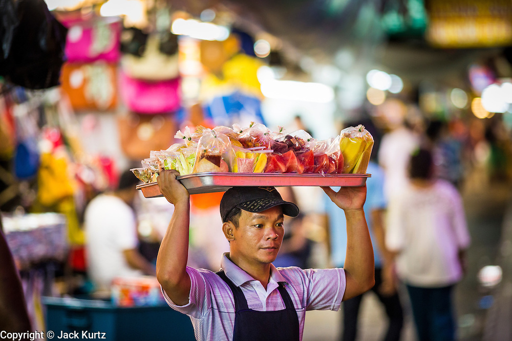 4 JUNE 2013 - BANGKOK, THAILAND:  A snack vendor walks through the Patpong Night Bazaar in Bangkok. Patpong was one of Bangkok's notorious red light districts but has been made over as a night market selling clothes, watches and Thai handicrafts. The old sex oriented businesses still exist but the area is now better known for its night shopping.      PHOTO BY JACK KURTZ