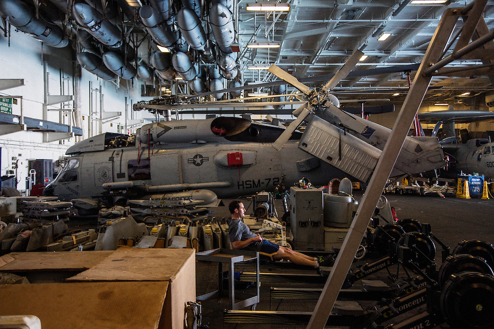 A sailor working out on a rowing machine on the hanger deck next to a helicopter undergoing service <br /> <br /> Aboard the USS Harry S. Truman operating in the Persian Gulf. February 25, 2016.<br /> <br /> Matt Lutton / Boreal Collective for Mashable