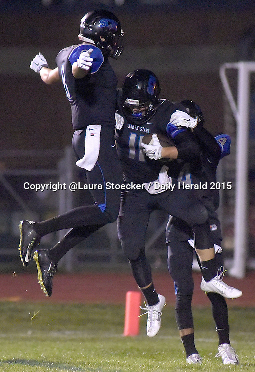 Laura Stoecker/lstoecker@dailyherald.com<br /> St. Charles North's Tyler Mettetal (center) celebrates his touchdown with teammates Griffin Hammer (left) and Jayson Reckards (right) in the second quarter Friday.