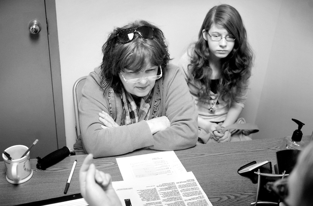 Linda and her daughter, Julianna, talk with social worker Leslie Anne Ramirez about their application for the Supplemental Nutrition Assistance Program - previously called food stamps.  After her husband Kirk has gone through a series of layoffs, the family now receives food from a local food bank and receives over $300 in assistance a month until Kirk finds other work.