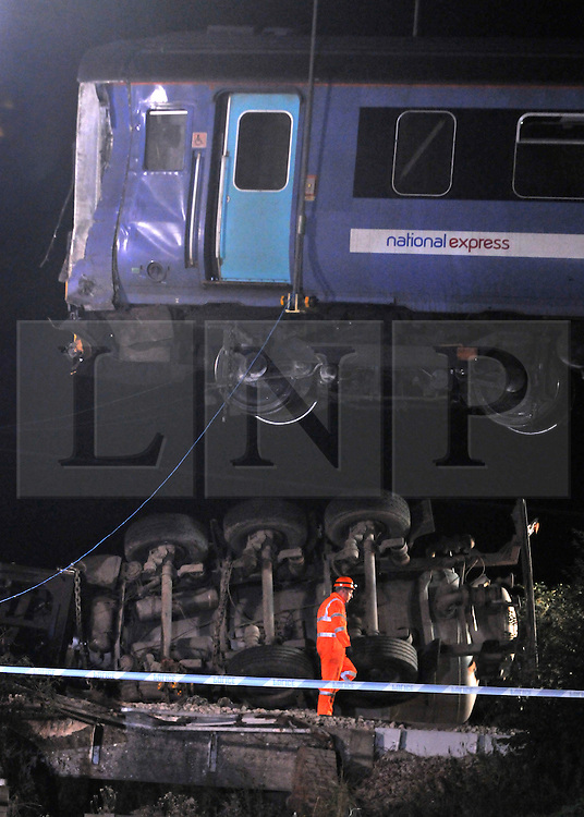 LITTLE CORNARD. SUDBURY. SUFFOLK.  Safety inspectors and Maintenance workers prepare to lift one of the two carriages above the truck involved in yesterday's level crossing train crash. Twenty one people were hurt, two seriously, when a train derailed in a crash with a lorry on a level crossing. in Little Cornard in Suffolk on 17th August. 18 August 2010. STEPHEN SIMPSON..