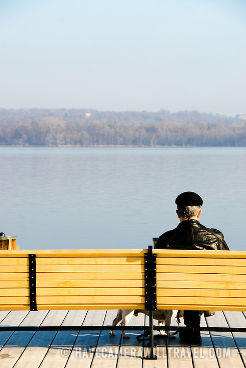 Man with his dog sitting on a bench at the Old Town Marina admiring the view over the Potomac River