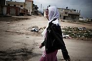 SYRIA - Al Qsair. A woman walks in a street as Al Asad Forces are shelling the city of Al Qsair, on February 23, 2012. ALESSIO ROMENZI