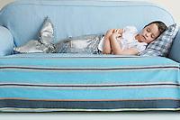 Young girl (5-6) wearing mermaid costume sleeping on sofa