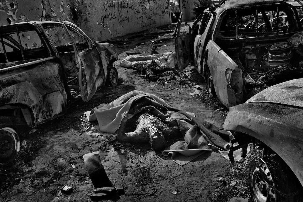 Disfigured bodies of men alleged to be part of Col. Muammar el-Qaddafi's bodyguards lie amid destroyed vehicles at the place Qaddafi's convoy was hitten by NATO airstrike and later he was assassinated by rebels, in the outskirts of Sirte, Libya, on October 20, 2011. Photo by Mauricio Lima for The New York Times