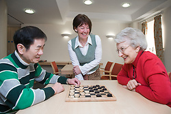Group of older people playing draughts in a care home,