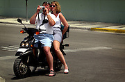 Tourists on a rental scooter taking pictures. Key West on the southern-most tip of Florida is a popular tourist destination, with a very different vibe to it than Miami.