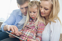 Parents and daughter using tablet computer in living room