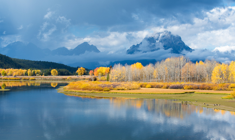 The Grand Teton mountains with fall leaves and the Snake River in the foreground
