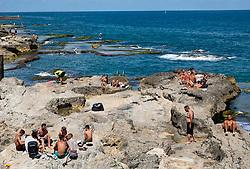 Men sunbathing on rocks at Ras Beirut beside The Corniche in Beirut, Lebanon.