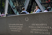 Modern English and ancient Latin marks the re-burial place of an unknown Roman girl near afternoon drinkers enjoying warm summer sunshine beneath the architecture of the Swiss Re building (aka The Gherkin), on 17th Juy 2017, in the City of London, England.