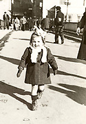 little girl walking in the street France ca 1950s