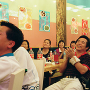 Chinese people watch the Olympic Games on television in a cafe near the Olympic Stadium, Beijing, during the summer Olympic Games. August 8 to August 24, 2008. Photo Tim Clayton