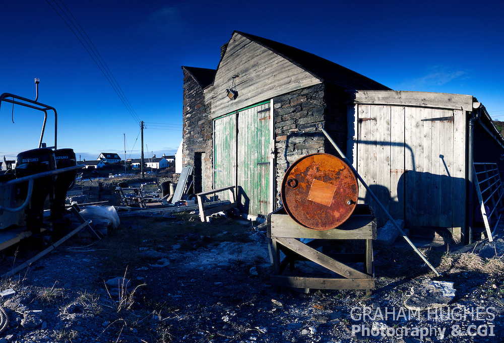 Work hut with boats and oil drum at Easdale Island in Scotland UK