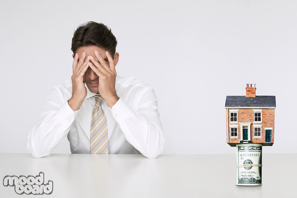 Worried businessman at table with house on top of bills representing increasing real estate rates