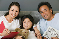 Family Relaxing Together in Bed reading portrait