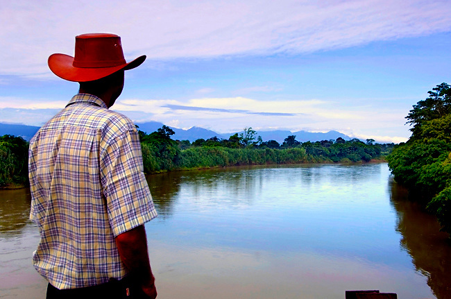 Costa Rican Man With Hat Enjoys Viewing The Rio Sucio In Costa Rica.